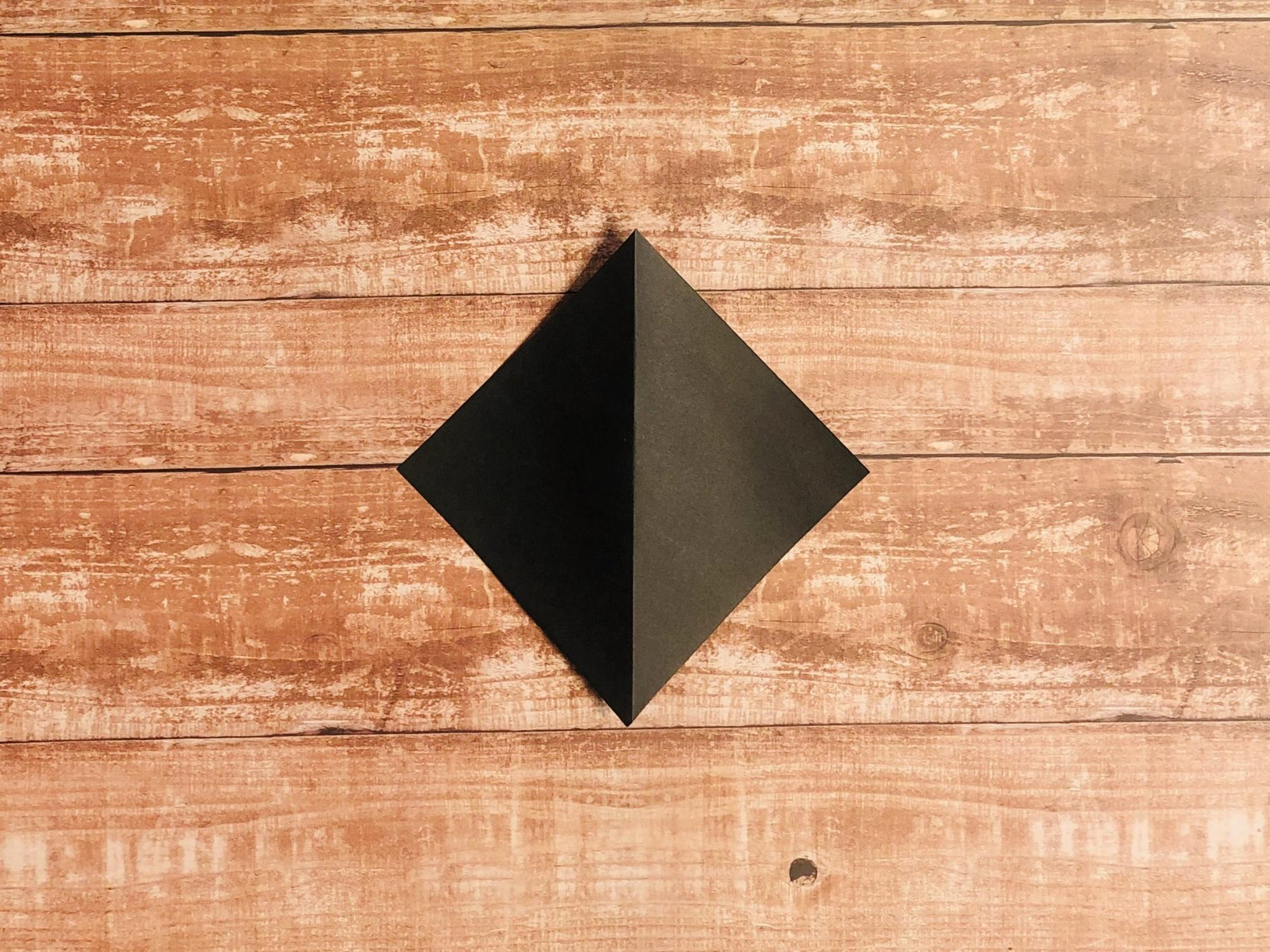 三角になるよう半分に折って、折り目をつけて戻します。