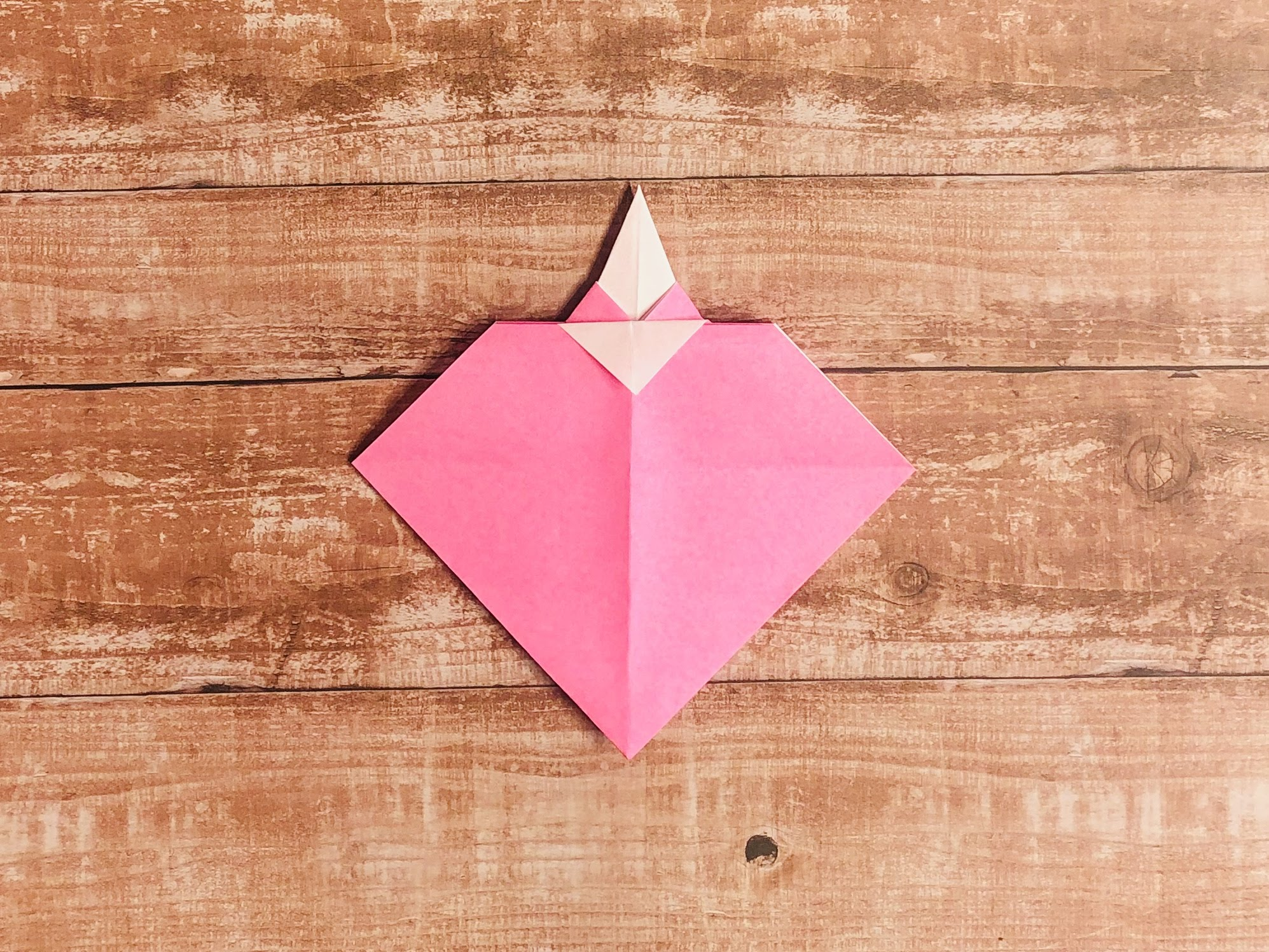 三角にはみ出た部分を手前に折ります。